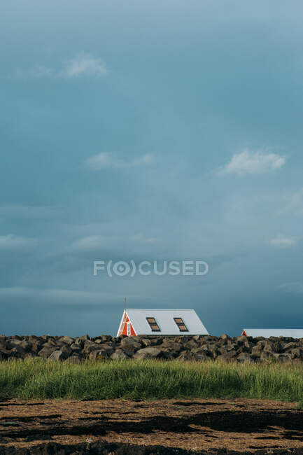 Picturesque landscape of cozy cute house in endless green field in Iceland in cloudy day in Iceland — Stock Photo