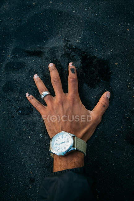 Hand of crop person with hand watch on big pile of black sand in Iceland — Stock Photo