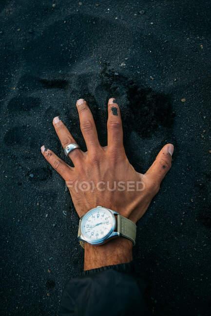 Erntehelfer mit Handuhr auf großem Haufen schwarzen Sandes in Island — Stockfoto