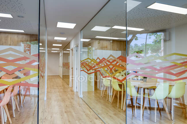 Светлый коридор с деревянным полом среди стеклянных стен светлых современных уютных офисных конференц-зон с удобными оранжевыми и желтыми стульями за большими деревянными столами — стоковое фото