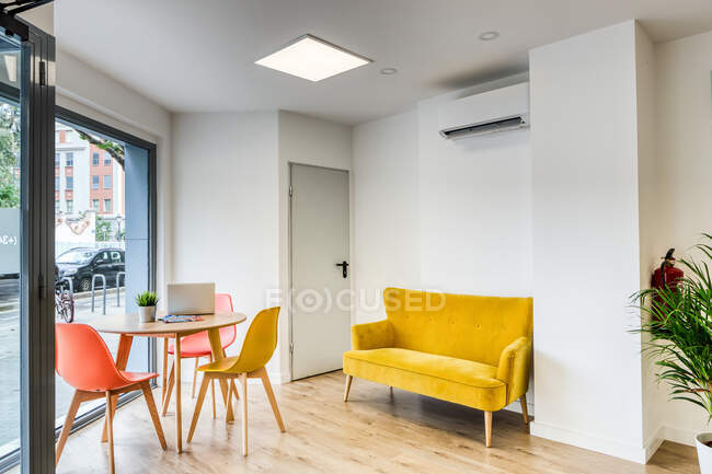 Modern simple interior design of light cozy spacious office with comfortable orange chairs at round wooden table and yellow sofa against white walls and big window — Stock Photo