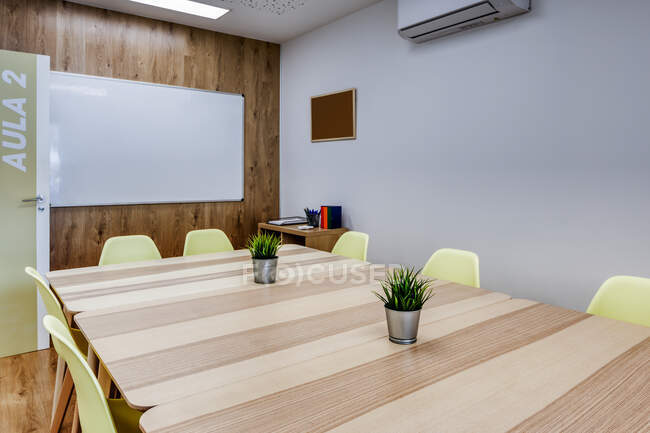Modern interior design of light spacious office zoned by glass wall with comfortable yellow chairs and gray bar stools at wooden tables — Stock Photo