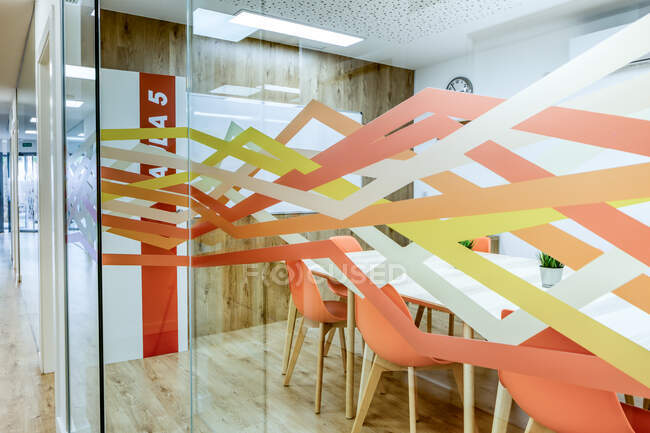 Light corridor with wooden floor among glass walls of light modern cozy office conference zones with comfortable orange chairs at big wooden tables — Stock Photo