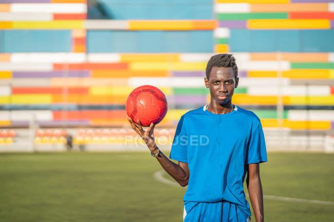 Jóvenes negros con balón de fútbol contra asientos del estadio - foto de stock