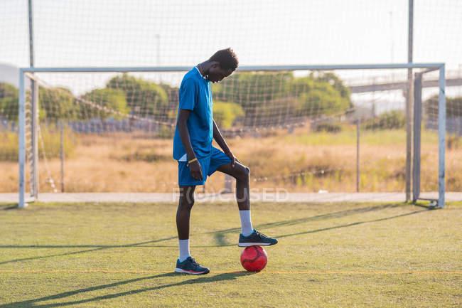 Futbolista negro con balón en el estadio - foto de stock