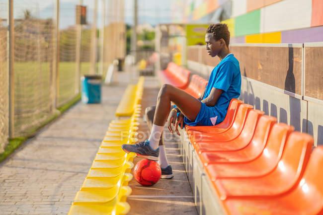 Vista lateral del futbolista afroamericano que descansa en los asientos del estadio - foto de stock