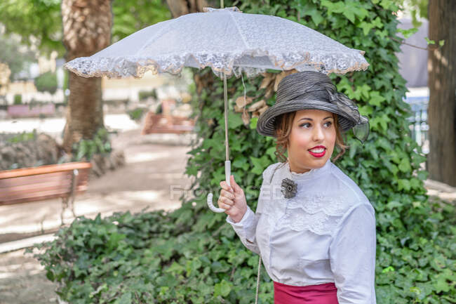 Vintage lady with parasol resting in garden — Stock Photo