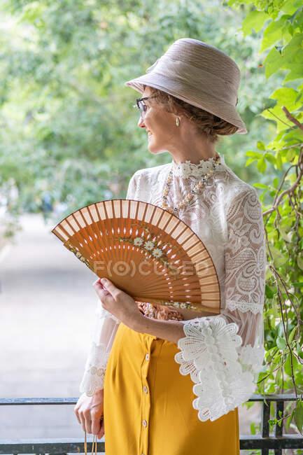 Женщина с ретро-вентилятором в парке — стоковое фото
