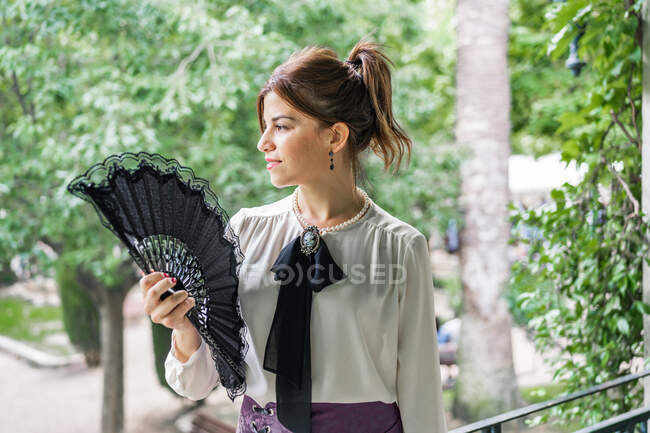 Woman with retro fan in park — Stock Photo