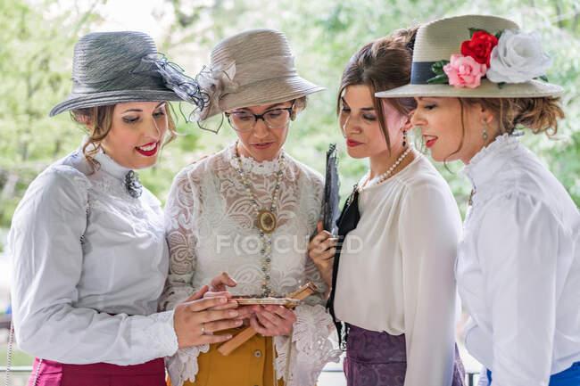 Весёлые женщины в ретро-костюмах улыбаются и просматривают смартфон, стоя в солнечный день в парке — стоковое фото