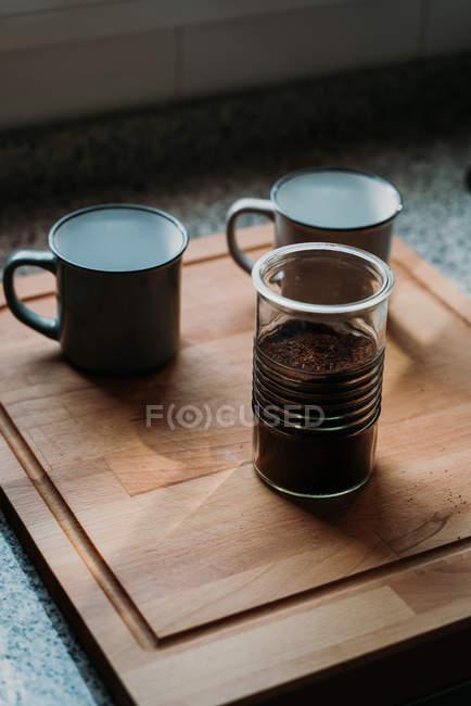 Canecas brancas esmaltadas vazias ao lado de garrafa de vidro de café moído na placa de corte de madeira acima do topo do contador cinza — Fotografia de Stock