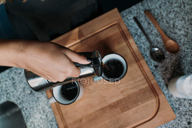 Hand of woman pouring coffee into enameled mugs in modern kitchen — Stock Photo