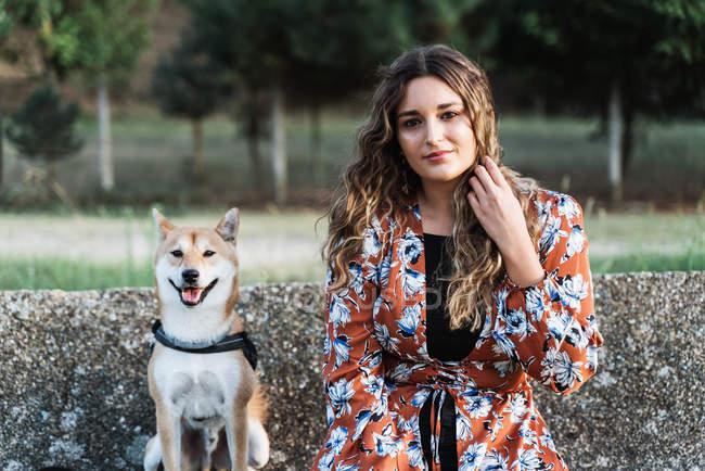 Donna affascinante dai capelli lunghi guardando la fotocamera con cane domestico seduto nelle vicinanze in giorno luminoso — Foto stock