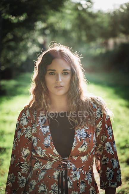 Encantadora mulher pensativa com cabelos longos encaracolados sonhador olhando para a câmera no parque verde em dia ensolarado — Fotografia de Stock