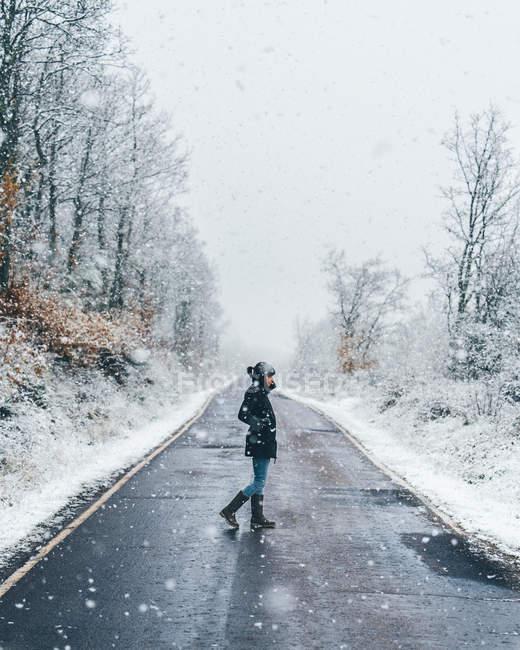 Seitenansicht eines Mädchens in schwarzer Jacke, das bei Schnee und trübem Winterwetter eine leere Landstraße überquert — Stockfoto