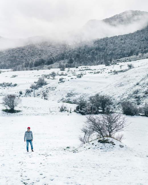 Lässiger Mann in roter Strickmütze mit gestreiftem Pullover und Jeans, der auf einem schneebedeckten Winterfeld spaziert — Stockfoto
