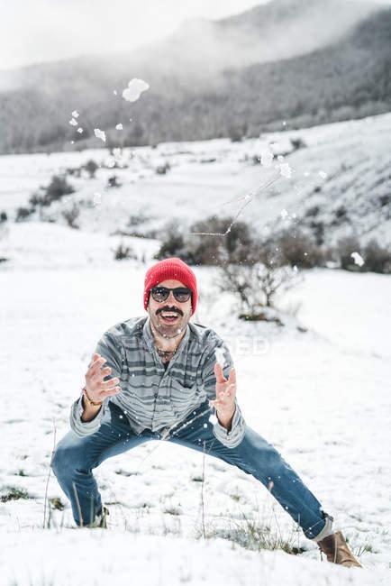 Berretto casual uomo in maglia rossa che gioca con la neve sul campo invernale con le colline — Foto stock