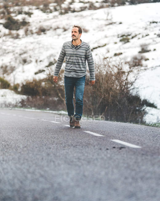 Adult male walking on country roadway with hills covered by snow on gloomy cloudy weather — стокове фото