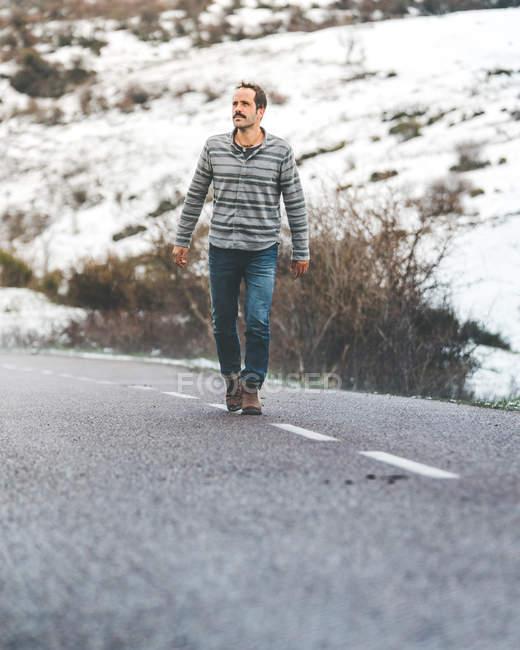 Erwachsener Mann läuft auf Landstraße mit schneebedeckten Hügeln bei trübem Wetter — Stockfoto