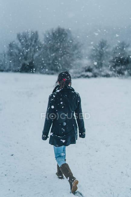 Vista posteriore della donna che indossa vestiti caldi camminando sul campo invernale con colline coperte di neve — Foto stock