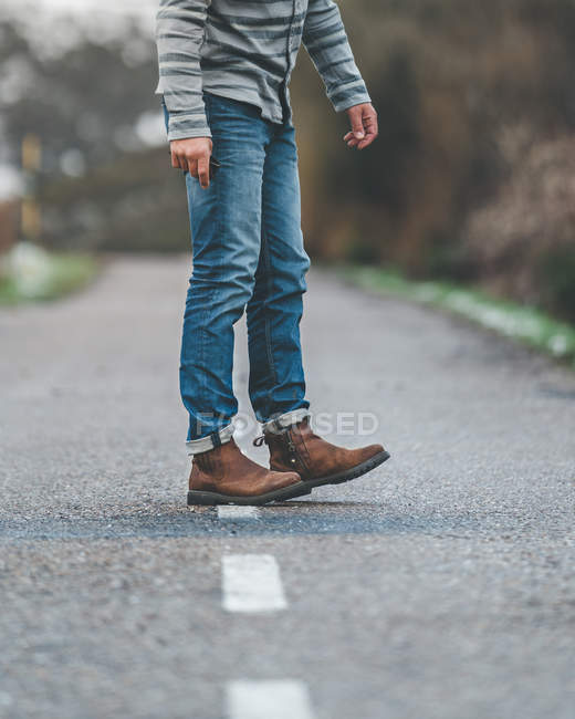 Male legs in jeans on country roadway on gloomy cloudy weather — стокове фото