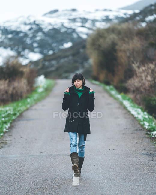 Jolie jeune femme en manteau noir et jean marchant sur une route de campagne vide avec des collines couvertes de neige — Photo de stock