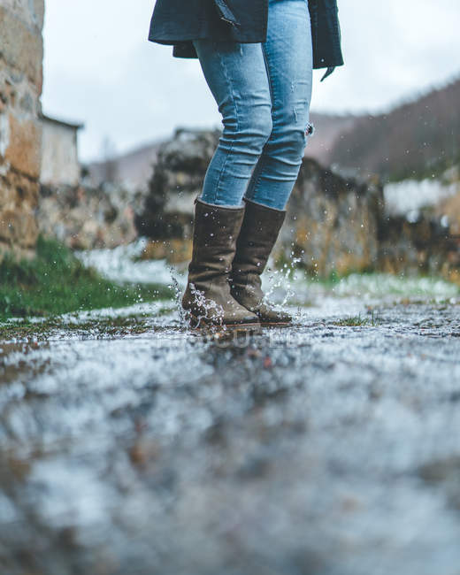 Female traveler in jeans and brown boots jumping on wet trail in autumn weather — стокове фото