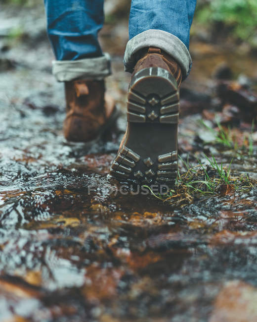Back view of male traveler brown boots walking on wet trail in autumn forest — стокове фото