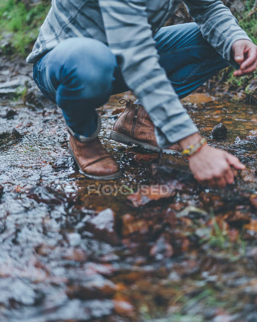 From below of male squatting on wet trail during walking in autumn forest — стокове фото