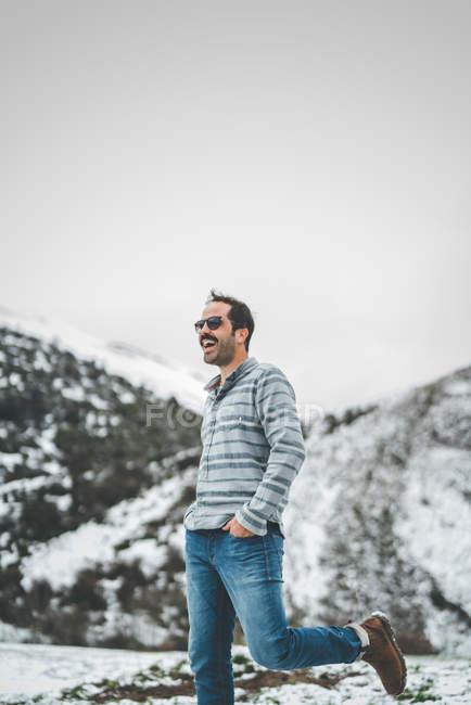 Lässiger Mann geht auf Winterfeld mit schneebedeckten Hügeln — Stockfoto