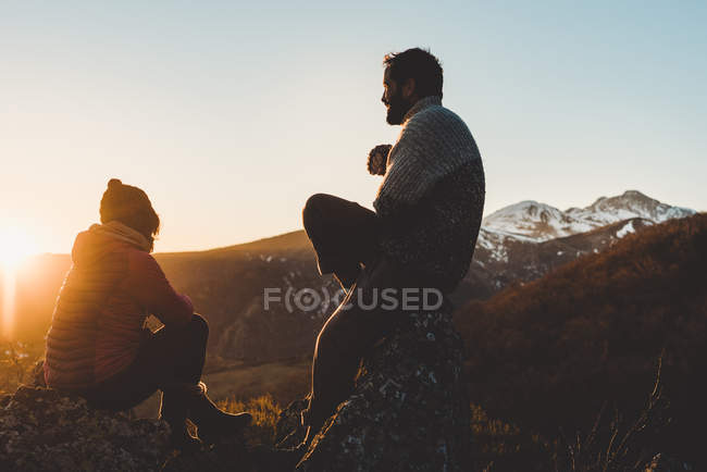 Silhouette of relaxed male and woman sitting in backlit on mountain top at sunset — Stock Photo