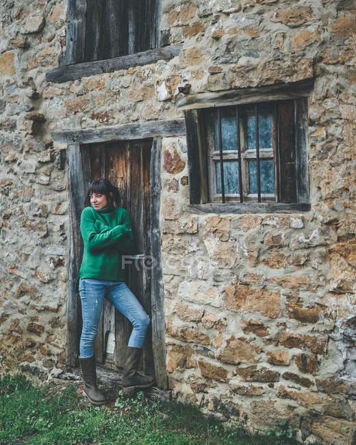 Donna casual in maglione verde in piedi con braccia incrociate accanto alla porta della vecchia casa di campagna in pietra — Foto stock