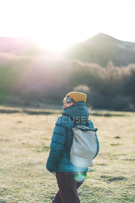 Повернення до нерозпізнаного мандрівника у теплому активному одязі з рюкзаком на сухій траві. — стокове фото