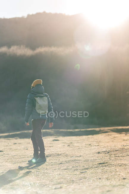 Rückansicht von unkenntlich gemachten Reisenden in warmer Aktivkleidung mit Rucksack über leeres, trockenes Grasfeld — Stockfoto