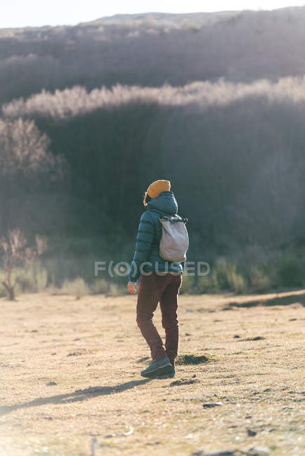 Back view of unrecognizable traveler in warm active wear with backpack crossing empty dry grass field — Fotografia de Stock