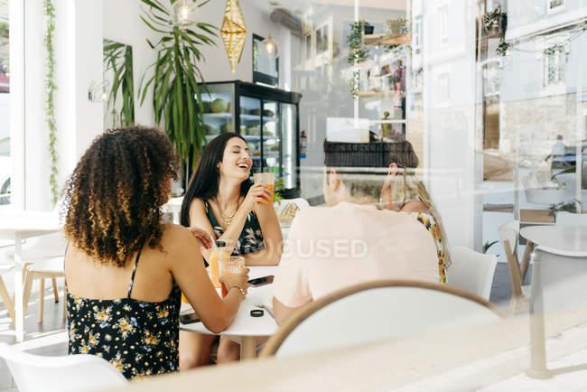 Разные друзья отдыхают с коктейлями, сидя в кафе — стоковое фото