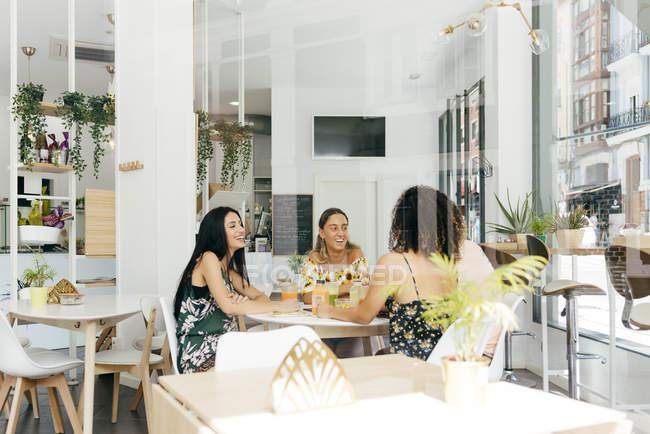 Разные друзья с коктейлями, сидящие в кафе — стоковое фото
