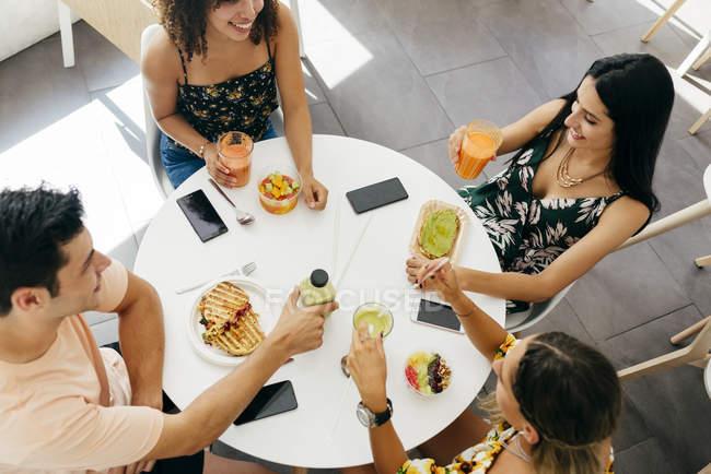 Разные друзья с рюмками с коктейлями — стоковое фото