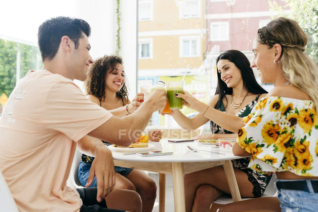 Diverse friends clinking glasses with smoothies — Stock Photo