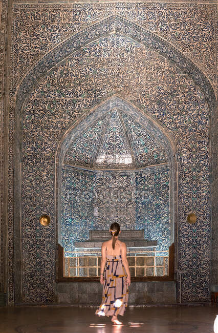 Vue arrière du touriste adulte en tenue décontractée debout contre la tombe en pierre dans le mausolée de Mahmud Pahlavan avec des arcs et mosaïque orientale bleue sur les murs à Khiva — Photo de stock