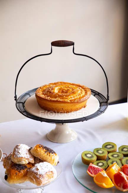 Сверху стильный стенд с вкусным пирогом на столе с пирогами и фруктовыми блюдами — стоковое фото