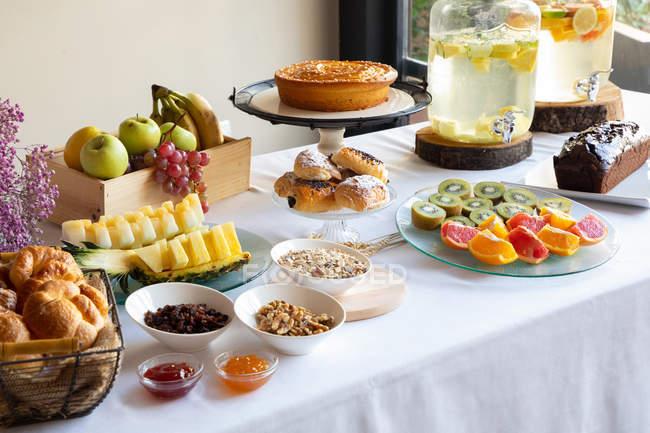 Vista lateral do jantar festivo com saborosa comida de padaria de frutas e elegantes margens de limonada na mesa decorada com flores lilás — Fotografia de Stock