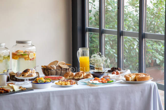 From above of appetizing sitting table for breakfast with bakery seafood sandwiches eggs and orange juice at stylish dinning room — Stock Photo