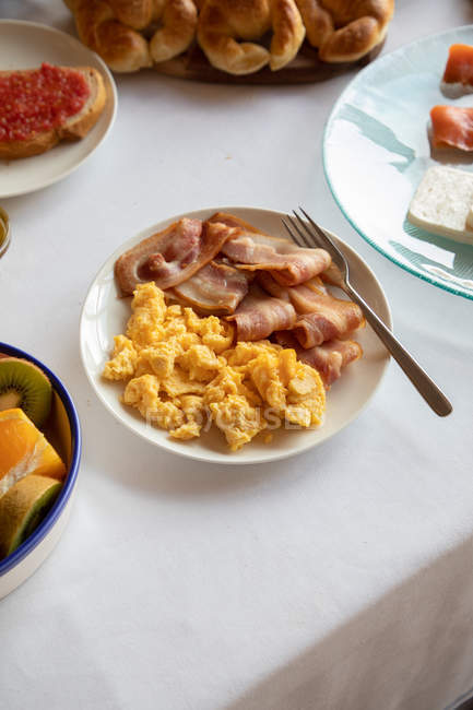 From above of delicious dish of bacon and coddled eggs on plate with fork on beautiful breakfast table — Stock Photo