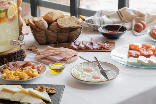 Von oben Blick auf die gemütliche Tischdekoration bestehend aus Spiegeleiern und Speck Lachskäse Mehl und Backwaren zu Hause — Stockfoto