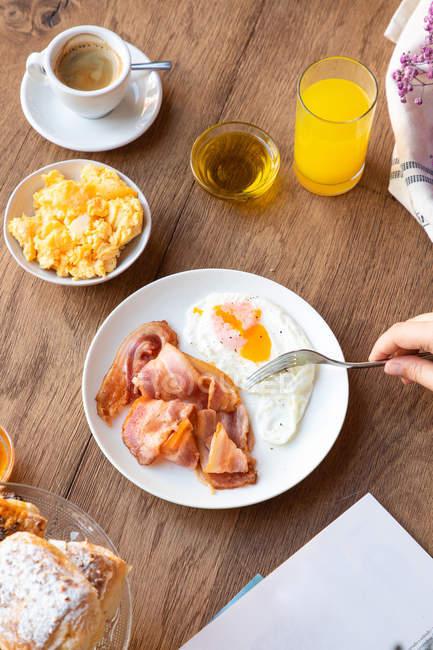 Da sopra persona coltura immergendo il pane in tuorlo di uova fritte con pancetta per la colazione e lettura libro a tavola servita — Foto stock