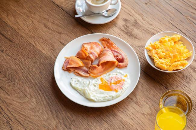 Сверху свежие жареные яйца с беконом в тарелке, подаваемые на завтрак с соком и кофе — стоковое фото