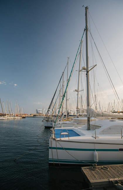 Exquisitos yates amarrados en aguas tranquilas en un día brillante en Port Valencia, España - foto de stock