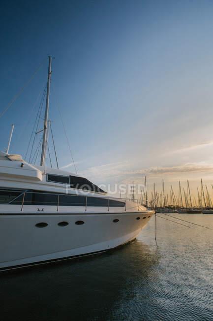 Botes blancos cómodos amarrados en agua brillante a través del sol brillante en Port Valencia, España - foto de stock