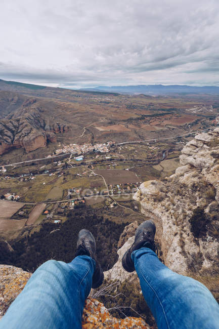Feet of person in jeans sitting on edge of mountain with breathtaking view at scenic valley — Stock Photo